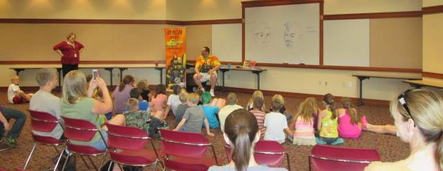 Jim showing kids how to design characters at New Prairie Public Library, summer 2015